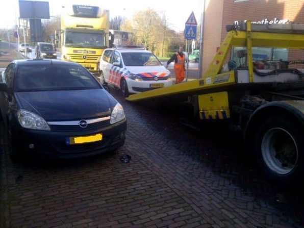 De politieauto word afgesleept door een bergingsbedrijf
