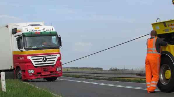 De vrachtwagen word uit de berm gehaald