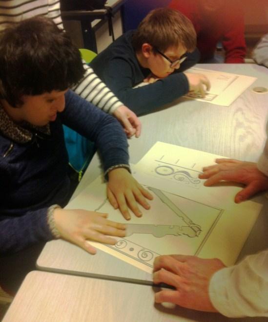 Des élèves de l'INJA parcourent une planche en relief de l'enluminure. Photo Médiathèque de Troyes Champagne Métropole