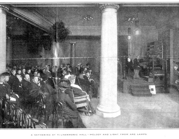 An audience at Telharmonic hall enjoying a concert of Telharmonic music played through carbon-arc lamps.
