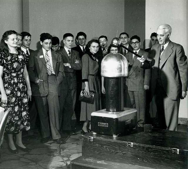 "Dr. Richard Hitchcock of Westinghouse sits on top of ""junior"" the portable Van de Graaff generator"