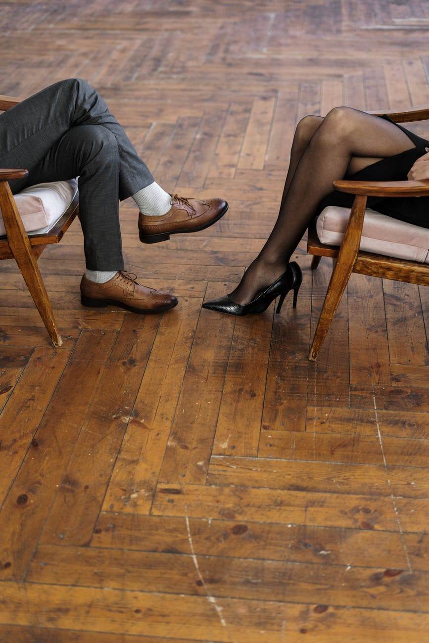 person in black leather shoes sitting on brown wooden chair