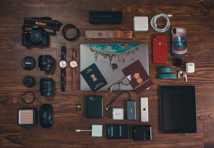 passports camera battery charger watches and cables on brown wooden surface
