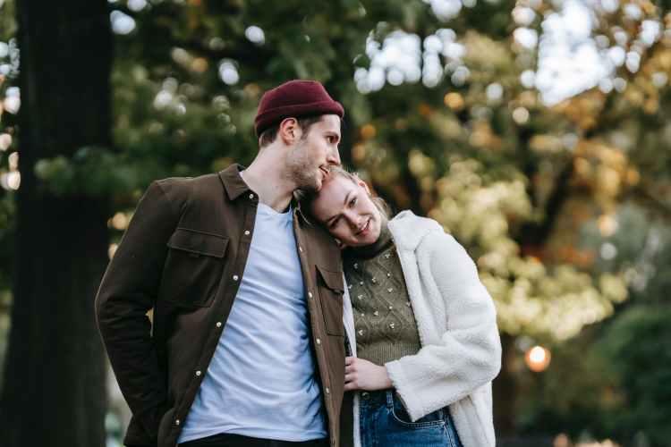 happy trendy couple hugging in park in sunlight