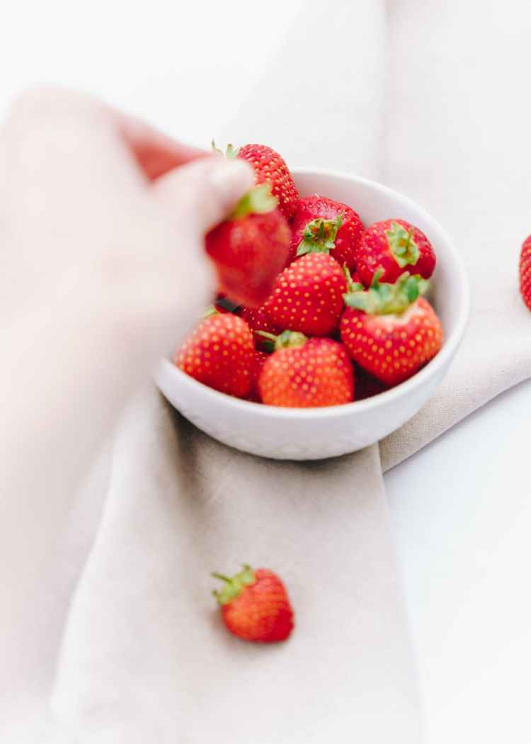 strawberries in plate on white surface