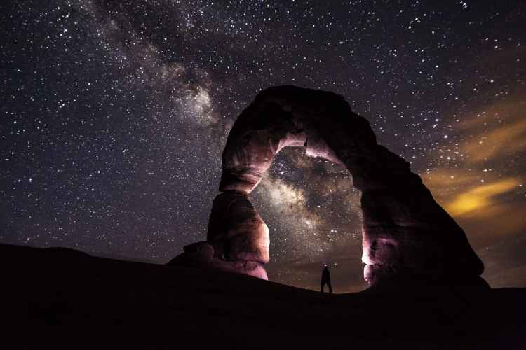 person under delicate arch at night