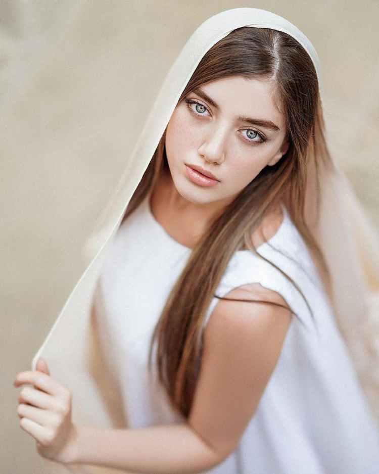 woman in white shirt covering her face with white textile