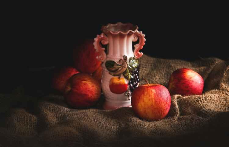 white vase beside apples