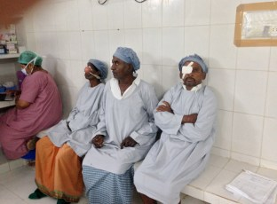 OR at Goutami Eye Hospital showing patient who just had surgery (far right with patch), next up, and on deck, for surgery (2 in the middle).  Eye surgeon and medical director Madhavi (far left) is taking care of some paperwork.