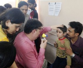 Dr. Hertle examines a child with nystagmus at Goutami Eye Hospital, Rajahmundry, India while the family, visiting ophthalmologists and staff look on.