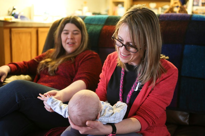 Home care nurse holds Riley while mom, Shelly watches
