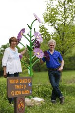 Artists Judith Spater and Stephen Canneto stand proudly next to the New England Aster at the F.A. Seiberling Nature Realm.