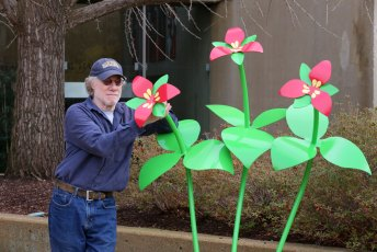 Artist Stephen Canneto with the Red Trillium sculpture outside E.J. Thomas Hall on the University of Akron campus