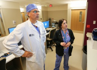 Dr. Milo and a surgery nurse check the new electronic patient status board before beginning surgery.