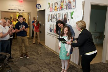 Neonatal respiratory therapist Kim Firestone gives 10-year-old Sophia a framed copy of her Wall of Hope picture.