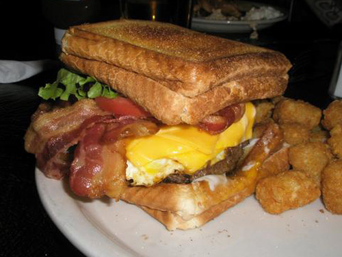 Double Bypass Burger A burger topped with five slices of bacon, four slices of cheese, two fried eggs, mayo, lettuce, tomato, and onion between two grilled cheese sandwiches. (Submitted by Kyle Korchran via thevortexbarandgrill)