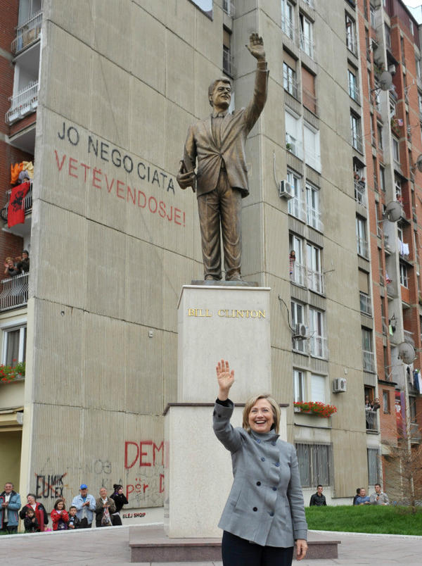 Hillary standing with creepy monument to Bill Clinton in Priština