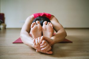 yoga pose seated - touching face to knees and hands to feet -Image by Jenia Nebolsina