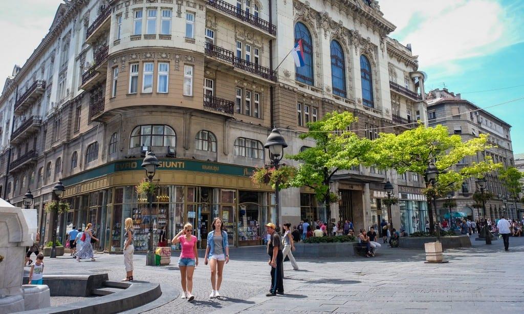 Two women walking on a city street in Belgrade.