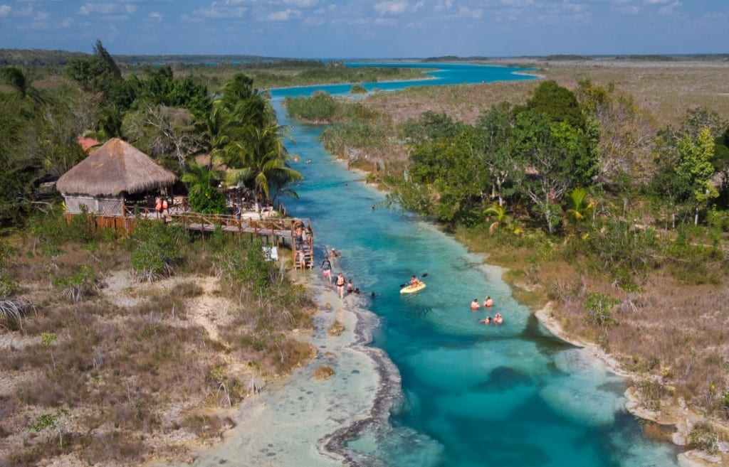 An aerial view of Los Rapidos: a turquoise river going through the green landscape, a small hut on shore, people swimming in the river.