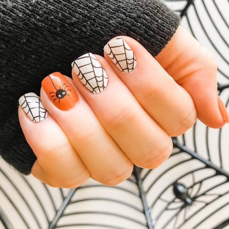 Short white and orange Halloween nails with spiderwebs