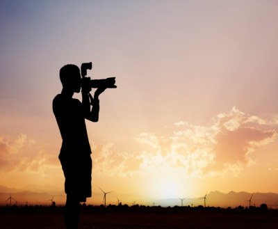 Man taking photos with camera at sunset