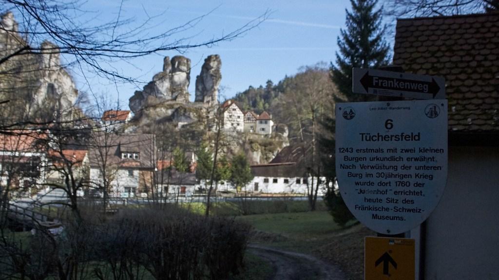 """Schild mit der Entstehungsgeschichte Tüchersfeld im Hintergrund Tüchersfeld. Auf dem Schild steht: """"Tüchersfeld. 1243 erstmals mit zwei kleinen Burgen urkundlich erwähnt. Nach Verwüstung der unteren Burg im 30-jährigen Krieg wurde dort 1780 der """"Judenhof"""" errichtet, heute Sitz des Fränkischen Schweiz Museums."""