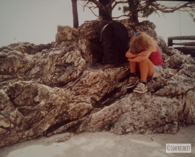 Mädchen mit verschränkten Armen und vergrabenen Gesicht sitzt auf einem Stein.