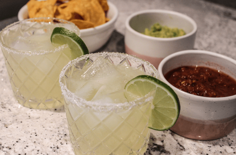 photo of a margarita on the rocks with chips, guacamole, and salsa