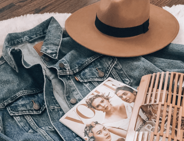 flatlay photo of denim jacket, wool fedora, basket bag, and magazine