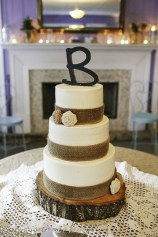 Burlap flowers on wedding cake topped with a B