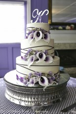 Deep purple calla lilies and ribbon on wedding cake
