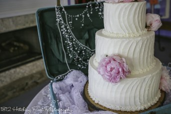 Pink peonies on vintage wedding cake in suitcase with pearls