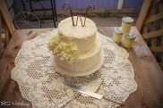 Rough iced wedding cake with wire initial topper