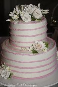 Pink swirl wedding cake with candy flowers