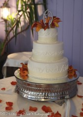 Wedding cake with cream ribbon and orange flowers