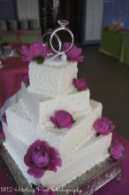Wedding cake with staggered square layers, pink peonies and diamond ring topper