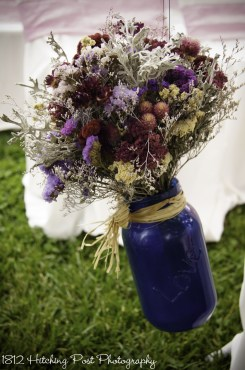 "Navy mason jars hang on aisle with ""Love"" on them and bride's provided dried bouquets"