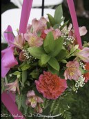 Galvanized bucket tied with pink ribbon and filled with fresh spring flowers