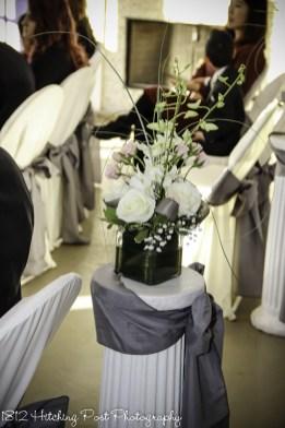 Centerpiece arrangement tops columns with gray sash for indoor winter wedding