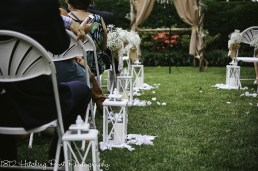 White lanterns with burlap bows for reserved aisles