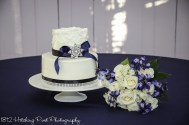 Navy bow on wedding cake with diamonds and brooch