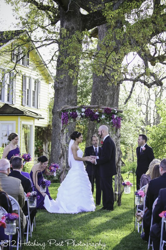 Wood arbor with deep purple and white silk flowers