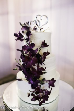 Live orchids in plum on wedding cake