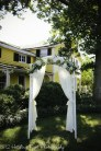 White arbor with white lace curtains
