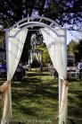 Bride walks through first arbor toward second