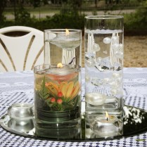 Trio of vases with live flowers, floating candle, and suspended pearls