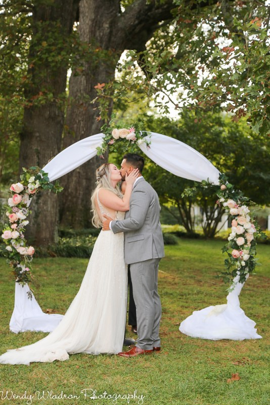 Circle arbor with white drape and silk blush flowers