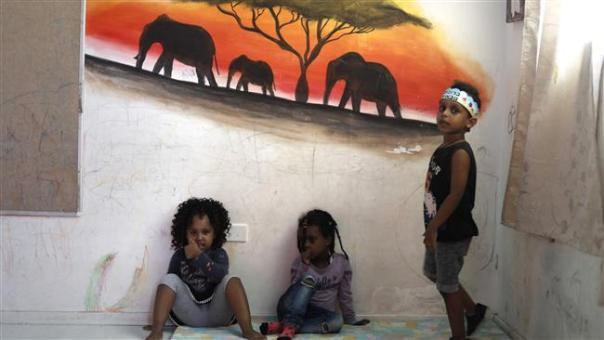 Children of Eritrean refugees play at a makeshift kindergarten in Tel Aviv on September 4, 2017. (Photo by AFP)