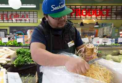 Produce employee Henry Rillo slices open a renkon, or lotus root